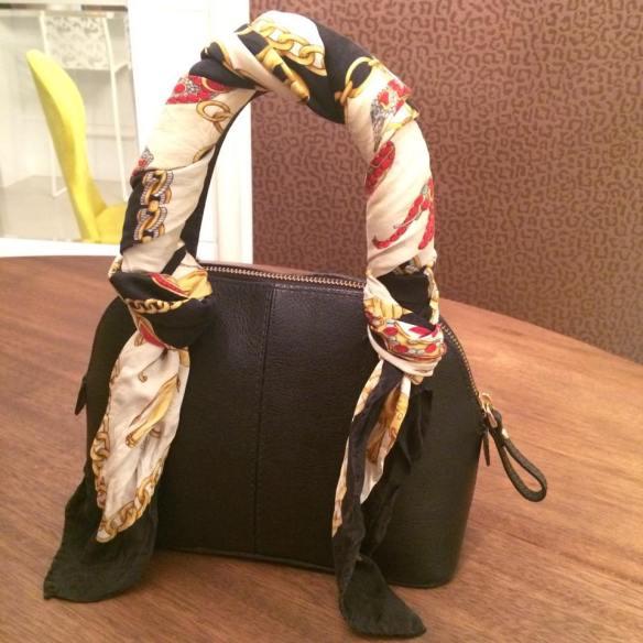 Enrole o lenço em toda a alça da bolsa, iniciando e finalizando com um nó.
