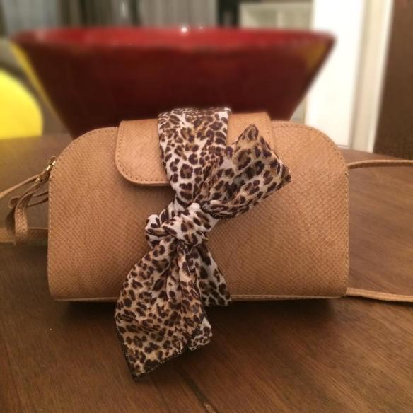 Um laço envolta da bolsa tira colo